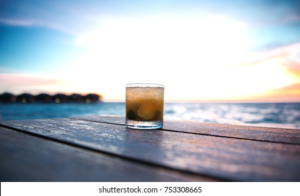ice cold cocktail in a beach bar on the maldives at sunset