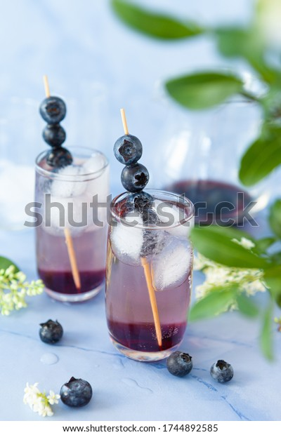Ice cold cocktail with blueberries and flower blossoms