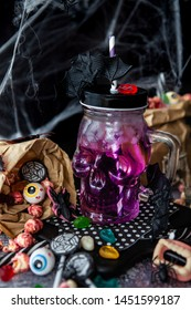 Ice cold cocktail and colorful sweets for Happy Halloween