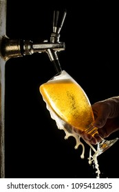 ice cold draft beer flowing from the glass, the bartender's hands