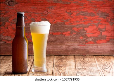 Ice cold frothy pale ale in a tall glass alongside an unlabelled beer bottle with long neck over a rustic wood background with peeling red paint and copy space