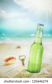 Ice cold green unlabelled bottle of refreshing lager or soda standing upright in the golden sand on a tropical beach under the hot rays of the summer sun