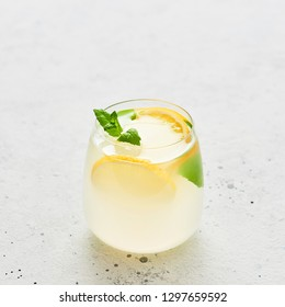 Ice cold summer drink. Traditional lemonade or mojito with lemon, mint and ice on white background. Copy space for text. Square crop.