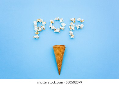ice cone and pop corns  making the word pop.Blue background.Flat lay
