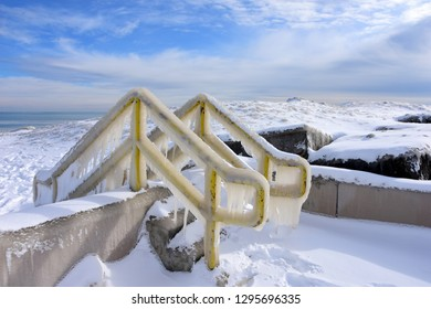 Ice covered handrails along the frozen shore of Lake Michigan off Kenosha Wisconsin on a January day.