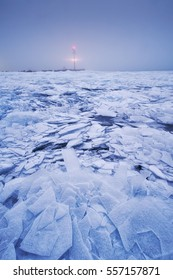 Ice cracks on the surface of a lake background lighthouse