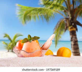 Ice Cream apricot , summer sundae with fresh fruits on wooden table with tropical beach.