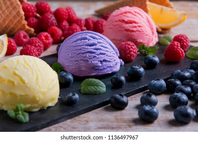 Ice cream assorted balls with lemon raspberry bilberry on a stone surface with pieces of fruit. Delicious  fresh fruits ice cream. Summer and Sweet menu