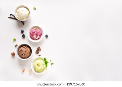 Ice Cream Assortment. Various ice creams and ingredients on white background, copy space. Frozen yogurt or ice cream in cups - healthy summer dessert.