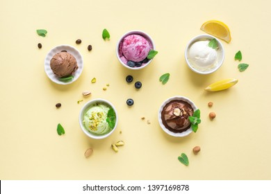 Ice Cream Assortment. Various ice creams in bowls on yellow background, top view. Frozen yogurt or organic ice cream - healthy summer dessert.