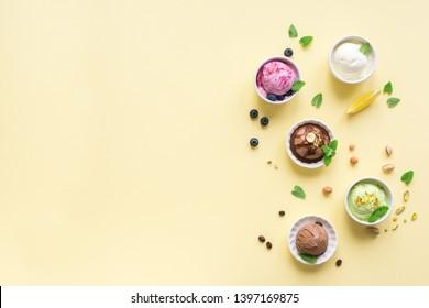 Ice Cream Assortment. Various fruit and berries ice creams on yellow background, copy space. Frozen yogurt or ice cream - healthy summer dessert.