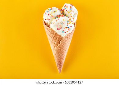 ice cream balls with colored sugar sprinkles in a Waffle Cone on a yellow Background. Vanilla ice cream in a waffle cone.