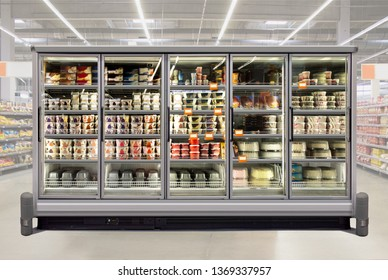 Ice cream and birthday cakes in a glass door freezer at supermarket. Suitable for presenting new packaging among many others. Front view.