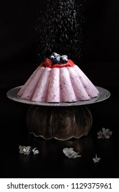 Ice cream cake with yogurt and berries under a rain of sifted icing sugar