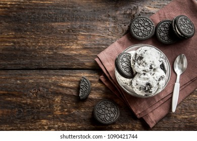 Ice cream with chocolate cookies. Cookies and cream homemade ice cream dessert on dark wooden background.