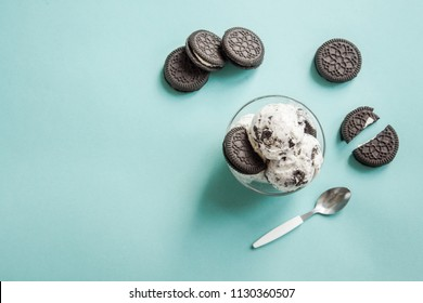 Ice cream with chocolate and cream sandwich cookies. Cookies and cream homemade ice cream dessert on blue background, copy space.