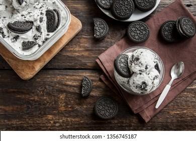 Ice cream with chocolate and cream sandwich cookies. Cookies and cream homemade ice cream dessert on dark wooden background.