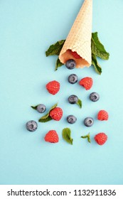 An ice cream cone with blueberries, raspberries and mint on a colorful background as a symbol of a refreshing summer fruity ice cream