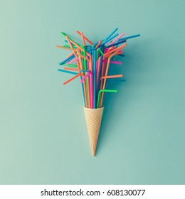 Ice cream cone with colorful drinking straws on bright blue background. Minimal food concept. Flat lay.