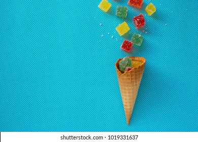 Ice cream cone with colourful jelly sweet. Top view delicious candy on blue turquoise background. Valentine's day elements. Summer love concept. Valentines concept. Minimal concept.