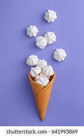 Ice cream cone with meringues on a purple background. Sweet summer concept. Top view. Flat lay