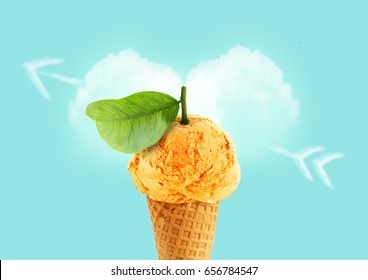 Ice cream cone of orange flavor with green leaf and cloud in love heart shape on blue sky.