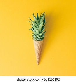 Ice cream cone with pineapple leaves on bright yellow background. Fruit and candy concept. Flat lay.