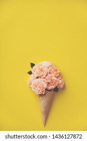 Ice cream cone with pink roses on yellow background. Summer minimal concept. Flat lay.