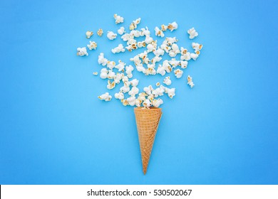 ice cream cone and pop corns in a pink background.Overhead.Flat lay