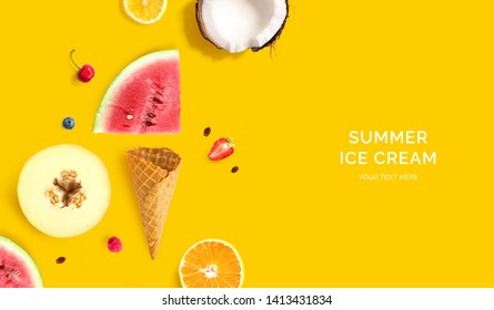 Ice cream cone with raspberry, blueberry, coconut, lemon, melon and watermelon. Flat lay. Food concept. Yellow background.
