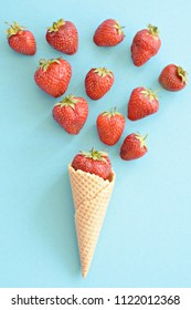 Ice cream cone with strawberries on a colored background