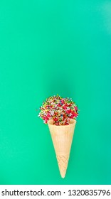 Ice cream cone with sweet sprinkles over green background - sweet concept, copyspace