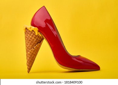 Ice cream cone's used as a high heel. Original footwear design concept. Isolated on yellow background.
