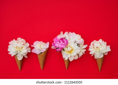 изображения:Waffle ice cream cones with white peony flowers on red background. Summer concept. Copy space, top view. Minimalism