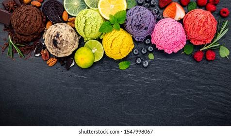 ice cream flavor ball blueberry ,lime ,pistachio ,almond ,orange ,chocolate and vanilla set up on dark stone background . Summer and Sweet menu concept.