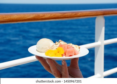 ice cream and fruits in front of railing and ocean
