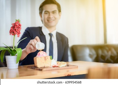 Ice cream pie topped with honey on a wooden table in a coffee shop. With the background scene is Asian male businessman.