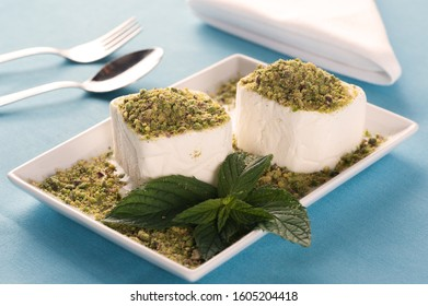 Ice cream with pistachios on white serving plate with spoon and fork