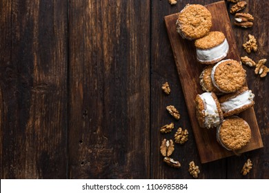 Ice cream sandwiches with nuts and wholegrain cookies. Homemade vanilla ice cream sandwiches on dark wooden background.
