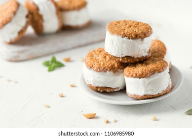 Ice cream sandwiches with nuts and wholegrain cookies. Homemade vanilla ice cream sandwiches on white background.