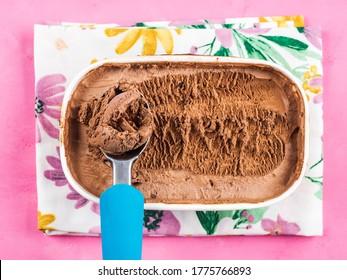 Ice cream scoop in chocolate ice cream tub on napkin on pink background. Closeup