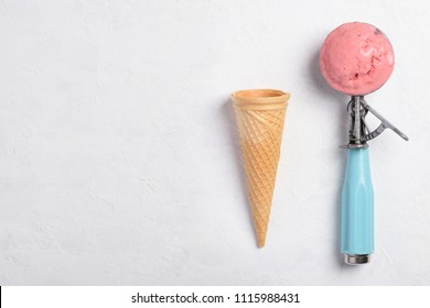 Ice cream spoon with homemade icecram scoop with wafer cone on white table background topview flatlay with copy space