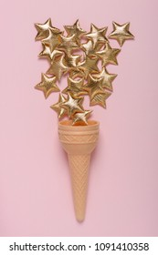 Ice cream sweet wafer cone with shiny golden stars on pink pastel background flatlay