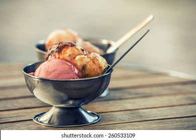 Ice cream in two retro metal bowls on a wooden table.