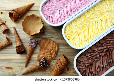 ice cream vanilla strawberry and chocolate in metal containers on wooden table background