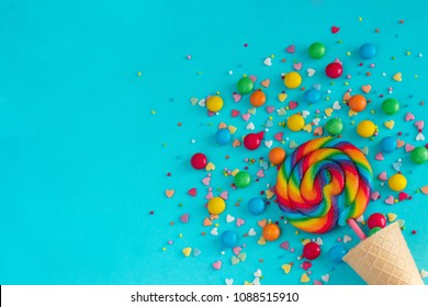 Ice cream waffle cone with colorful lollipop on stick, scattering of multicolored sweets and confectionery topping. Still life on blue background.Copy space,  Flat lay, Top view,  greeting card