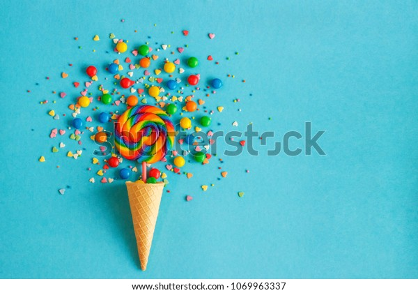 Ice cream waffle cone with colorful lollipop on stick, scattering of multicolored sweets and confectionery topping. Blue background