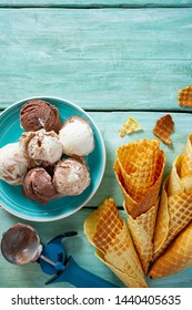 ice cream and waffle cones on turquoise wooden surface