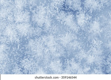 Ice crystals on a glass window during winter. Blue color