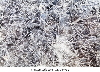ice crystals over frozen puddle in spring forest